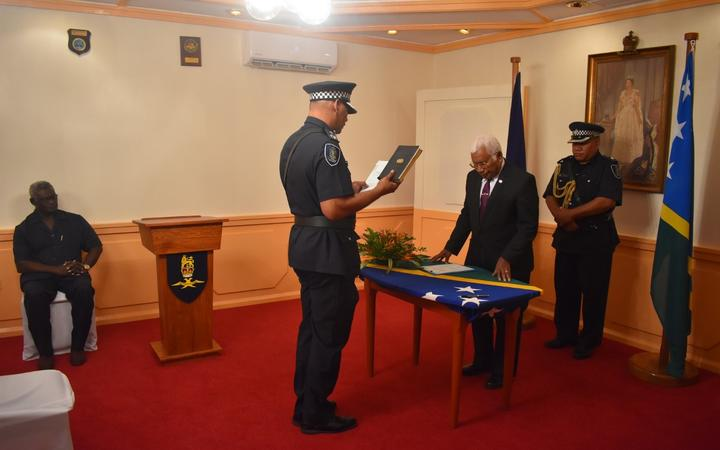 Solomon Islands police commissioner Mostyn Mangau taking his oath of affirmation before governor general Sir David Vunagi.