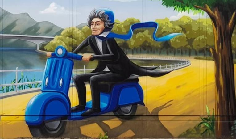 A caricature of Beethoven driving a blue motor scooter (and wearing a matching helmet) along a path next to a river.