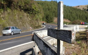 A cross stands on State Highway 5, marking the spot of a fatal crash on the road