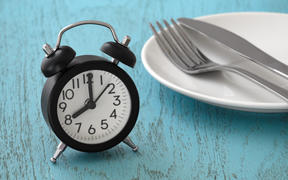 Clock with fork and knife on white plate, intermittent fasting, meal plan, weight loss concept