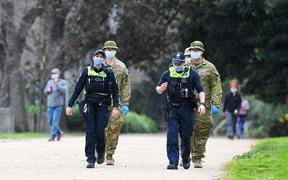 Police officers and soldiers patrol a popular running track in Melbourne on August 4, 2020 after the state announced new restrictions as the city battles fresh outbreaks of the COVID-19 coronavirus.