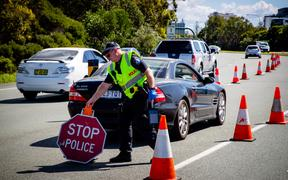 A Queensland police officer moves a stop sign at a vehicle checkpoint on the Pacific Highway, along the state's border with New South Wales, in Brisbane on April 15, 2020.