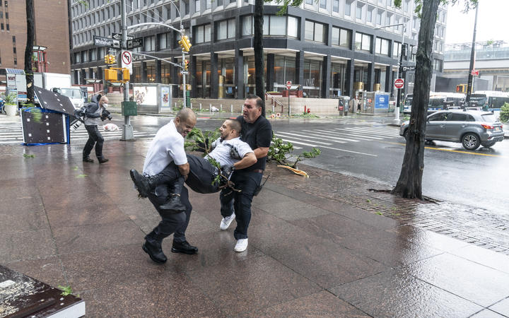 Co-workers carry injured maintenance worker by downed by strong wind tree after tropical storm Isaias lashes out New York City.