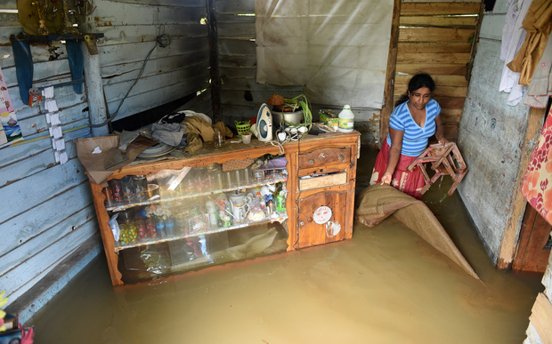 A Sri Lankan woman wades through floodwaters inside her home in Kelaniya suburb of the capital Colombo.