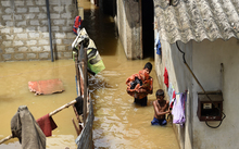 Sri Lankan youths wade through floodwaters as they go about their daily chores.