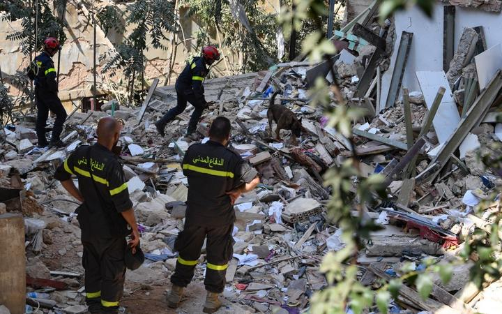 Members of the Lebanese civil defence look on as French rescuers use a dog to search for victims and survivors amidst the rubble of a building in the Gemayzeh neighbourhood on August 6, 2020, two days after a massive explosion in the Beirut port shook the capital.