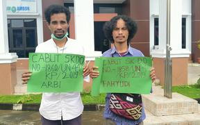 Two Indonesians protest the expulsion of four students from Khairun University for their role in a Papua human rights protest. The protest is outside the Ambon state administrative court where the students are challenging the expulsion.