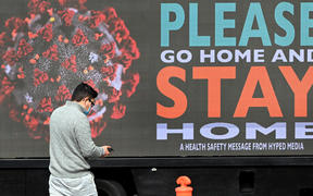 A man walks past a sign on a truck in Melbourne, as the city enforces strict lockdown restrictions.
