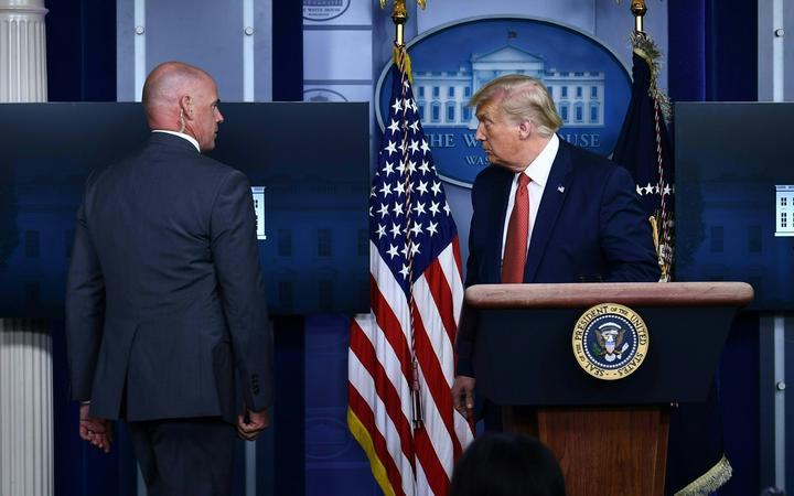 US President Donald Trump is being removed by a member of the secret service from the Brady Briefing Room of the White House in Washington, DC.