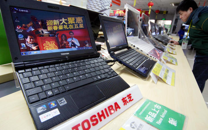 A customer shops for Toshiba laptop computers at a home appliance store in Nantong city, east China's Jiangsu province, 28 January 2011.