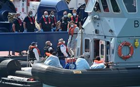 "UK Border Force officers come to meet migrants, believed to have been picked up from boats in the Channel, from Coastal patrol vessel ""HMC Speedwell"", in the port of Dove."