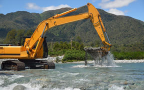 digger shifting shingle to deepen the channel in a flowing river, Westland, New Zealand