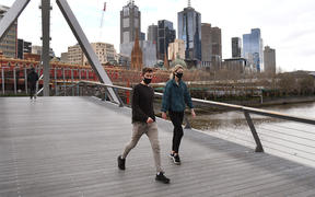A couple walks on a footbridge over the Yarra River in the Southbank district of Melbourne on 12 August 2020 during the city's Covid-19 lockdown.