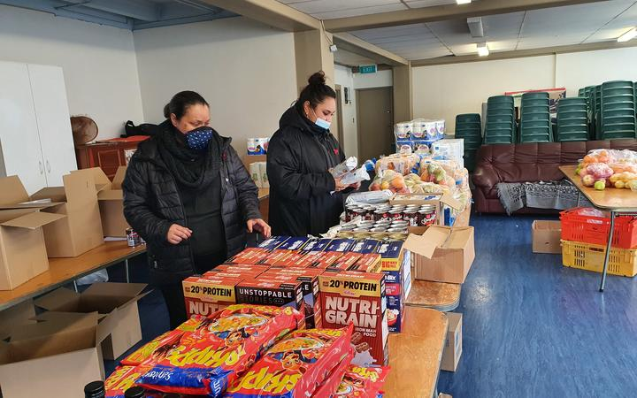 Emeline Afeaki-Mafile'o (left) and Melenaite Lausi'i prepare food parcels for their community organisation Affirming Works in Ōtāhuhu.