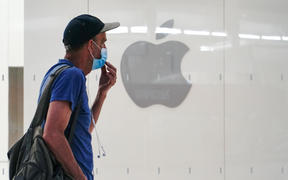 A man wearing a mask past an Apple store in New York City.