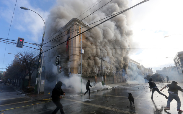 A security guard died when masked protestors burnt a pharmacy and supermarket.