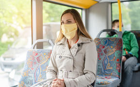 Woman using public transport during Covid-19 crisis wearing face mask.