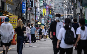 Pedestrians wearing face masks walk on a street in Seoul on August 24, 2020