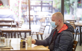 Man in restaurant wearing face mask to protect against Covid-19.