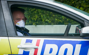 An Auckland Police officer sitting in his car wearing a mask looking at the camera. Covid 19
