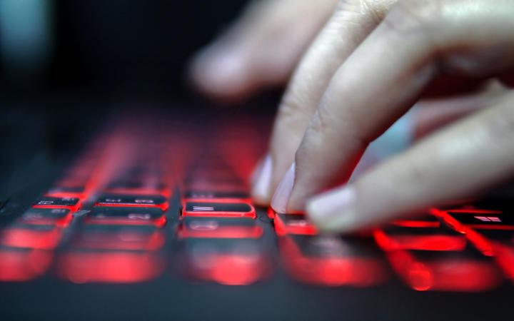 Aemilius Cupero News: Teenage Hacker Girl Attacks Corporate Servers in Dark, Typing on Red Lit Laptop Keyboard. Room is Dark