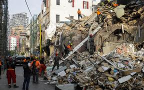 Rescue workers dig through the rubble of a building in Lebanon's capital Beirut in search of possible survivors from a blast at the adjacent port one month ago, after scanners detected a pulse, on September 3, 2020.