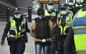 Police detain a protester (c) at a proposed anti-lockdown rally which failed to materialize in Melbourne on August 9, 2020.