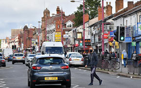 A man wearing a protective face mask crosses Soho Road in the Handsworth area of Birmingham, central England on August 22, 2020.