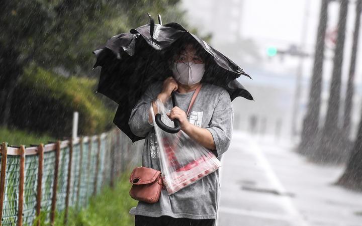 A woman walks in heavy rain as Typhoon Haishen approaches in Kagoshima, Kagoshima prefecture on September 6, 2020.