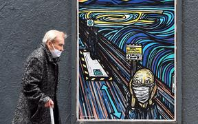 An elderly pedestrian wearing a face mask or covering due to the COVID-19 pandemic, walks past graffiti depicting the subjects within famous artworks, but wearing masks, in Glasgow.