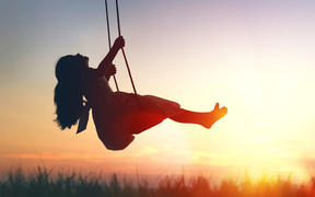 Happy laughing child girl on swing in sunset summer.