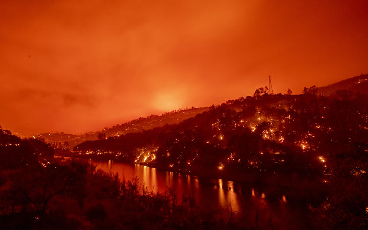 In this long exposure photograph, flames set ablaze both sides of a segment of Lake Berryessa during the Hennessey fire in the Spanish Flat area of Napa, California on 18 August, 2020.
