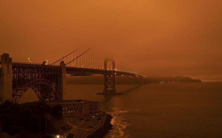 Cars drive along the San Francisco Bay Bridge under an orange smoke filled sky at midday in San Francisco, California on 9 September, 2020.
