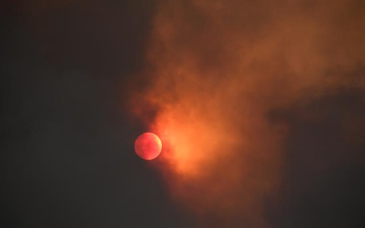 The sun is seen behind smoke from the Bobcat fire rising above in the Angeles National Forest above Duarte, California on 7 September, 2020.