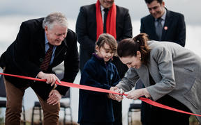 Labour Party leader cuts the ribbon with a girl, and Taupō Mayor David Trewavas during the leader's election campaign on 10 September, 2020.