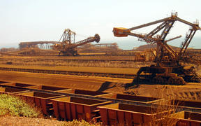 (FILES) This file photo taken on March 4, 2010 shows remote-controlled stackers and reclaimers moving iron ore to rail cars at Rio Tinto's Port Dampier operations in Western Australia's Pilbara region.