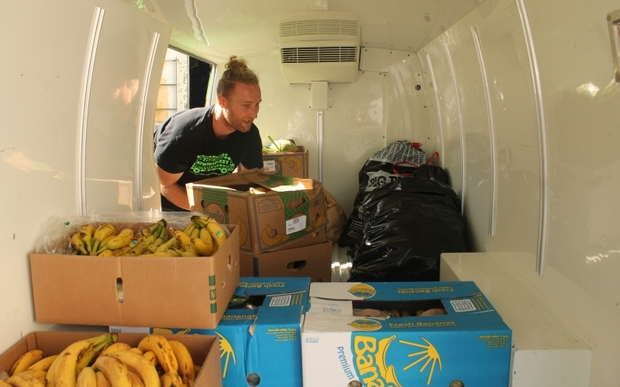 An image of Sam Mentink loading donated food into the Kiwi Harvest van.