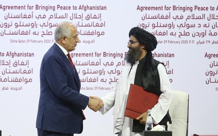 US Special Representative for Afghanistan Reconciliation Zalmay Khalilzad (left) and Taliban co-founder Mullah Abdul Ghani Baradar shake hands after signing the peace agreement between US, Taliban, in Doha, Qatar on 29 February, 2020.