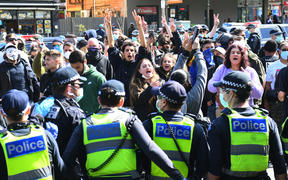 Anti-lockdown protesters chant slogans at Melbourne's Queen Victoria Market during a rally on 13 September