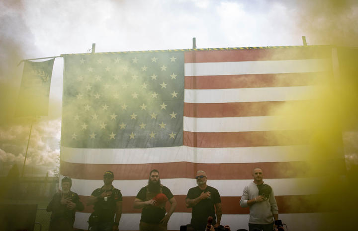 Yellow smoke fills the air as an American flag is raised at the start of a Proud Boys rally at Delta Park in Portland, Oregon on September 26, 2020.