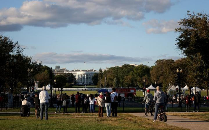 WASHINGTON, DC - OCTOBER 02: Bystanders look on as Marine One, the presidential helicopter, waits on the south lawn at the White House to carry U.S. President Donald Trump to Walter Reed National Military Medical Center October 2, 2020 in Washington, DC.