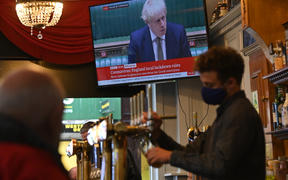 A television screens UK Prime Minister Boris Johnson speaking in the House of Commons, as customers sit at the bar of the Richmond Pub in Liverpool.
