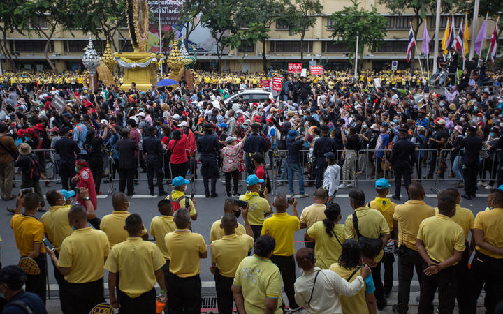 Pro-democracy protesters walk towards Government House as people dressed in pro-monarchy yellow t-shirts look on, Bangkok, 14 October 2020.