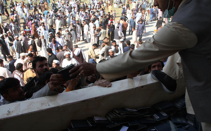 Afghans gather to collect token needed to apply for visas to Pakistan near the Pakistani consulate at an open stadium in Jalalabad city, Afghanistan.
