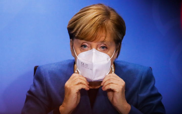 28 October 2020, Berlin: Chancellor Angela Merkel puts on her face mask at the end of a press conference in the Chancellery after a meeting with the prime ministers of the Länder on how to proceed in the corona pandemic.