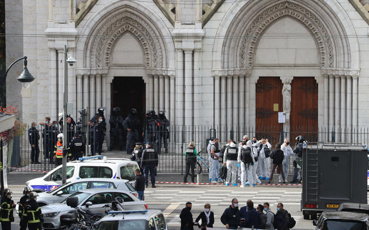 French members of the elite tactical police unit RAID enter to search the Basilica of Notre-Dame de Nice as forensics officers wait after a knife attack in Nice on October 29, 2020.