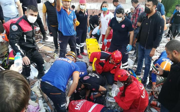 Rescuers search for survivors at a collapsed building after a powerful earthquake struck Turkey's western coast and parts of Greece, in Izmir, on October 30, 2020.