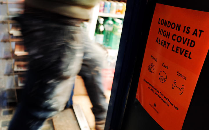 A man passes a notice warning of the current 'high' alert level for covid-19, taped at the entrance to a newsagent on Old Compton Street in Soho in London, England