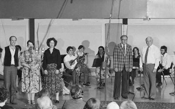 Douglas Lilburn (fourth from righ, in checked jacket), Ashley Heenan (2nd from right on stage), and members of the Schola Musica at a special broadcast concert honouring Douglas Lilburn on his 65th birthday, in Symphony House, Willis Street, Wellington. November 1980.