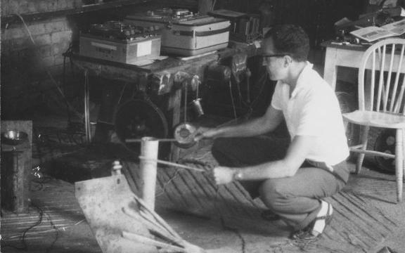 Douglas Lilburn recording the sound of struck sheets of steel and other items on to magnetic tape, in a barn in Wiltshire, England, circa 1963.